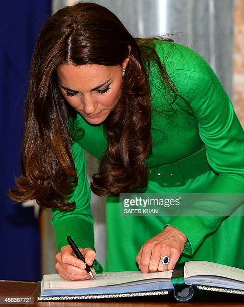 Catherine, the Duchess of Cambridge, signs a visitors' book following a reception at the Parliament House in Canberra on April 24, 2014. Britain's...