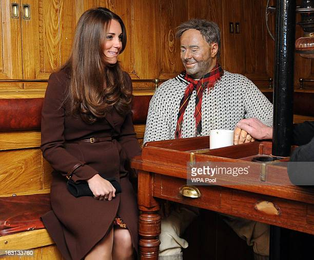 Catherine The Duchess of Cambridge sits next to a dummy of the Ship's Mate at the Skipper's Table during her tour of the National Fishing Heritage...
