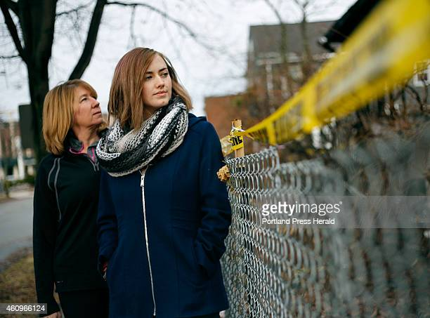 Catherine Wilson left and Grace Damon look over a fence at the remains of house on Noyes Street where a fire claimed the lives of six young people...