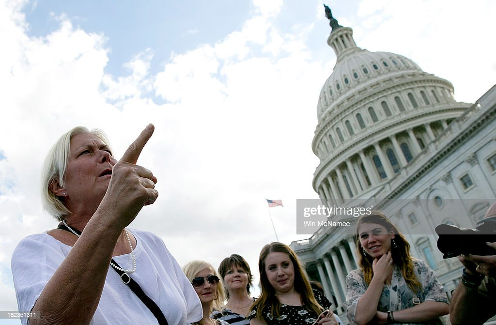 Catheryn Carroll, of Washington DC, berates members of the House Republican caucus while they hold a press conference on the steps of the U.S. Senate September 29, 2013 in Washington, DC. Republican members of the House were holding a press conference to protest the U.S. Senate not being in session today to avert a government shutdown. The House of Representatives passed a continuing resolution with language to defund U.S. President Barack Obama's national health care plan yesterday, but Senate Majority Leader Harry Reid has indicated the U.S. Senate will not consider the legislation as passed by the House.