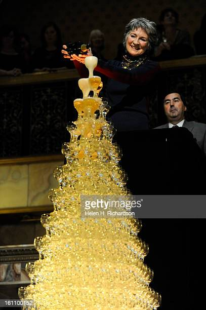 Cathey Finlon pours one of the four bottles of champagne into the towering cascade The 23rd Champagne Cascade held each year at the Brown Palace...