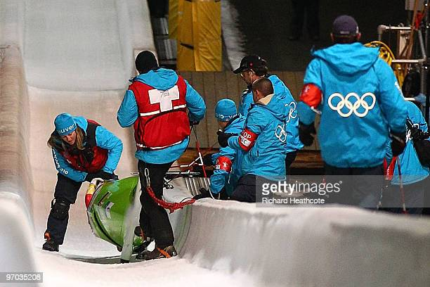 Cathleen Martini of Germany 2 is helped fom the track after they crashed out team mate Romy Logsch of Germany fell from the back of the bobsleigh...