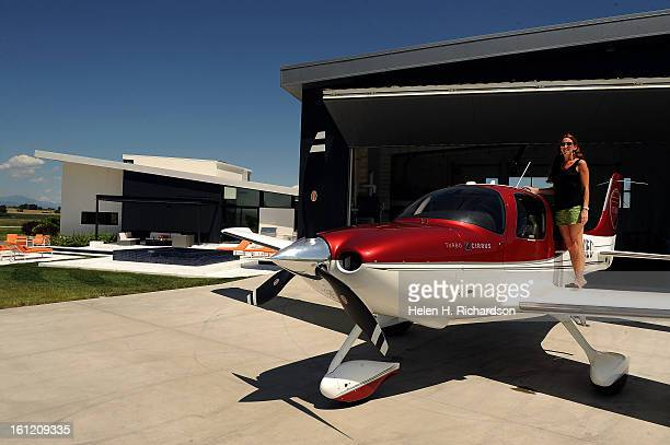 Cathleen Van Buskirk stand on the wing of her Cirrus SR22Turbo plane She has been flying for 5 1/2 years Her house is at left This is the home of...