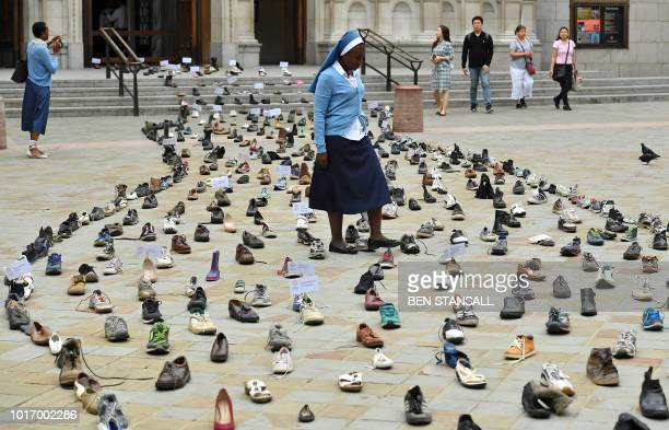 TOPSHOT Catholic Agency For Overseas Development's Sister Clara from Zambia walks through shoes displayed outside Westminster Cathedral in central...