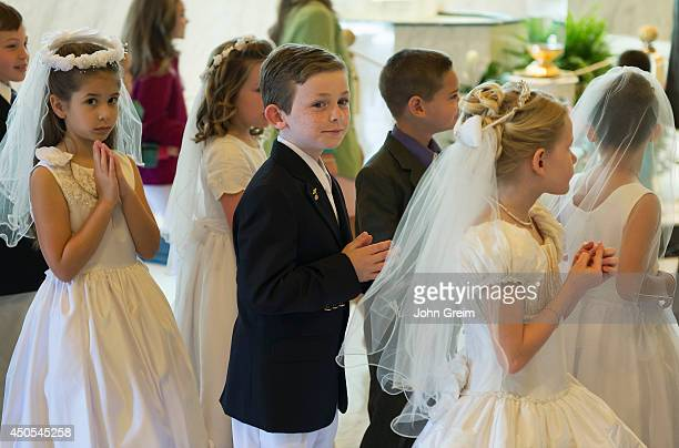 Catholic boys and girls receiving the sacrament of first holy communion