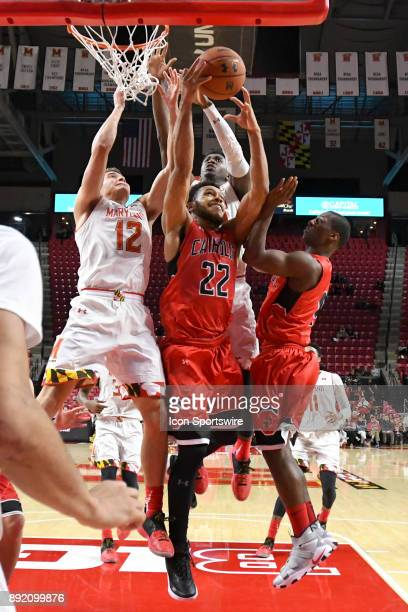 Catholic Cardinals forward Jay Howard fights for a second half rebound with Maryland Terrapins guard Reese Mona on December 12 at Xfinity Center in...