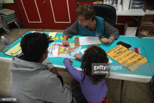 Catholic Charities volunteer at the Immigrant Respite Center shows a Salvadorian father and daughter a map of the United States on March 16 2017 in...