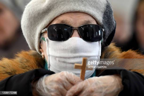 Catholic Christian believer wearing nose and mouth face masks amid concerns over the spread of the COVID19 the novel coronavirus attends the Sunday...