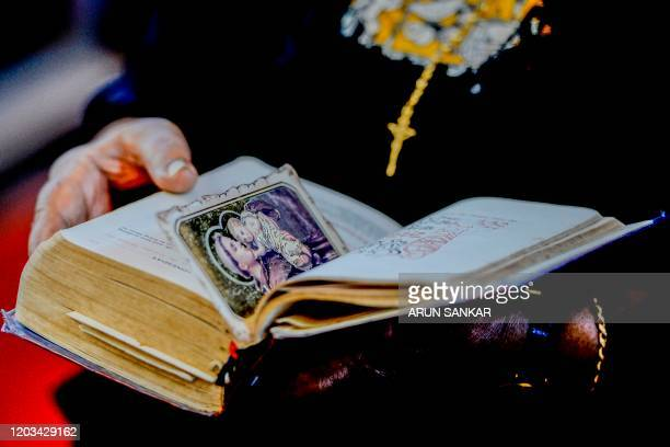 A Catholic Christian devotee holding a bible with a portrait of infant Jesus offers prayers during an Ash Wednesday service at St Thomas Cathedral...