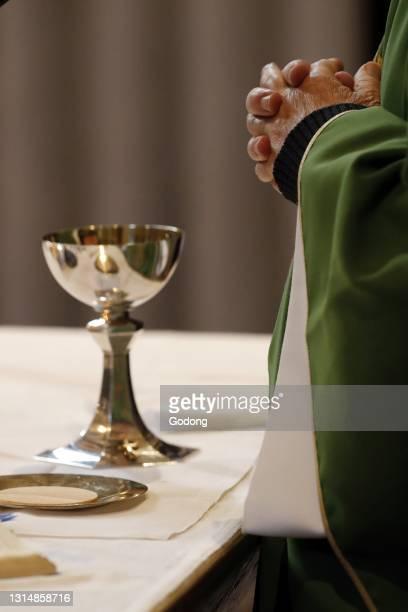 Catholic church during covid-19 epidemic. Sunday mass. Priest at eucharistic celebration. Sallanches. France.