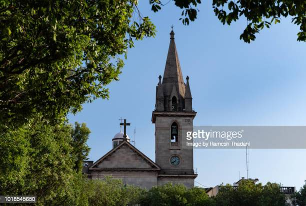 catholic church of st. sebastian, framed by trees - clock tower stock pictures, royalty-free photos & images