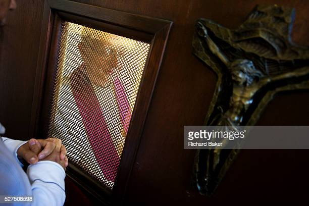 A Catholic confessional between a penitent parishioner and her local priest at St Lawrence's Catholic church in Feltham London While kneeling to face...
