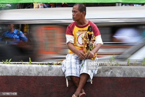 A Catholic devotee holding his replica of the Black Nazarene waits for the blessing of the replicas to start near Quiapo church in Manila on January...