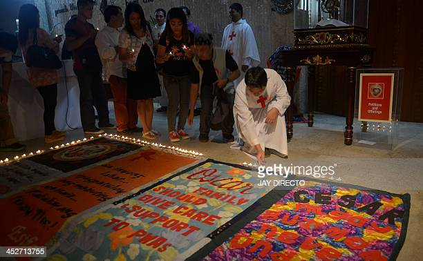 A Catholic devotee lights candles around quilts made by victims of HIVAIDS who died of complication because of HIVAIDS in a church in suburban Manila...
