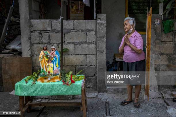 Catholic devotee stands next to palm fronds and religious icons placed on a table outside her home as she waits for a priest to be blessed with holy...