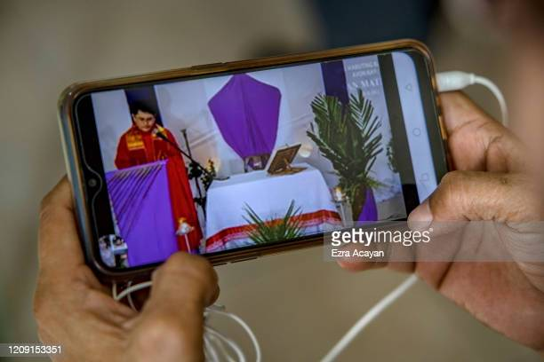 Catholic devotee watches an internet livestream of Palm Sunday services on a mobile phone on April 5 2020 in Quezon city Metro Manila Philippines...