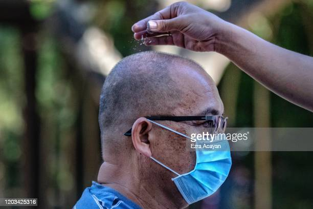 Catholic devotee wearing a protective mask has his head sprinkled with ash during Ash Wednesday services at a church on February 26 2020 in Paranaque...