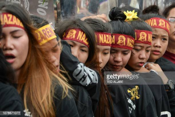 Catholic devotees carry a replica of the Black Nazarene during the blessing of the replicas near Quiapo church in Manila on January 7 ahead of the...