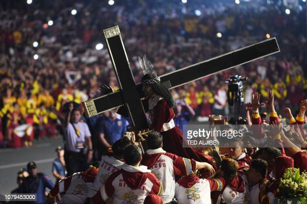Catholic devotees carry the statue of the Black Nazarene to a carriage at the start of the annual religious procession in honour of the Black...