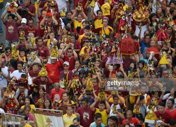 Catholic devotees carrying replicas of the Black Nazarene walk during the blessing of the replicas near Quiapo church in Manila on January 7 ahead of...