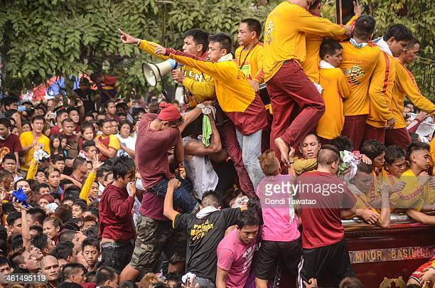 Catholic devotees climb the carriage carrying the Black Nazarene on January 9 2014 in Manila Philippines Devotees march barefoot as a sign of...