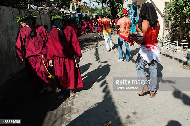 Catholic devotees flail themselves with wooden whips as a form of penance during holy week on April 2 2015 in Mabalacat town in Pampanga province...
