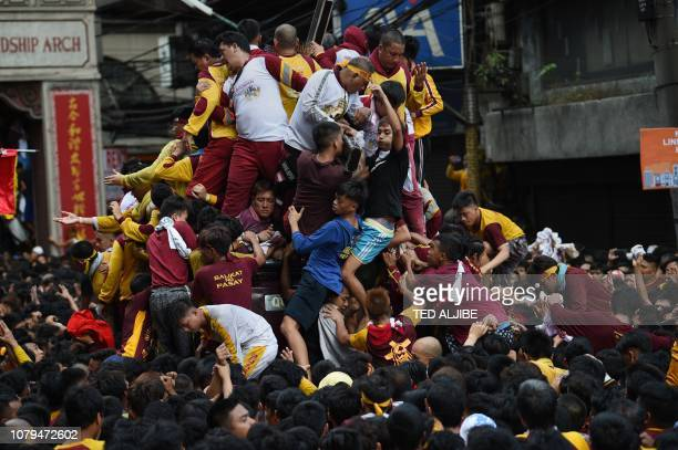 Catholic devotees jostle with each other as they try to touch the Black Nazarene statue on a carriage during the annual religious procession in...