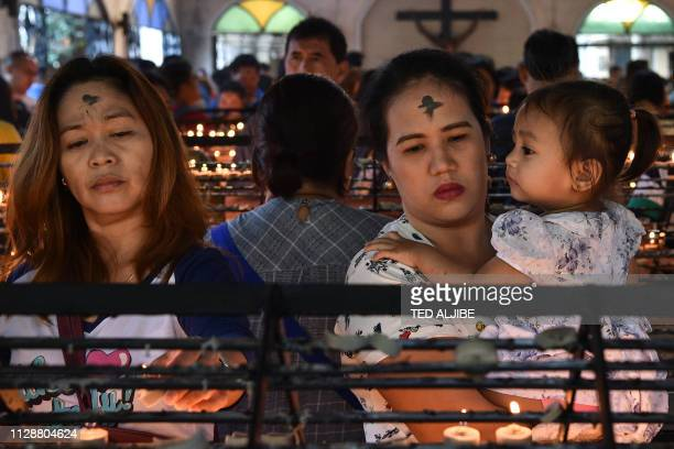 Catholic devotees pray on 'Ash Wednesday' at a church in Manila on March 6, 2019. - The 40-day period of Lent begins on Ash Wednesday, with Catholics...