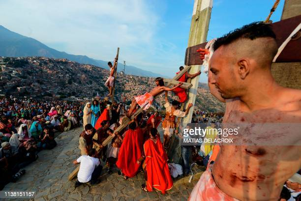 Catholic devotees reenact the crucifixion of Jesus Christ during a Good Friday procession in Caracas' Petare shantytown on April 19 2019