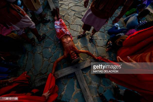 TOPSHOT Catholic devotees reenact the crucifixion of Jesus Christ during a Good Friday procession in Caracas' Petare shantytown on April 19 2019
