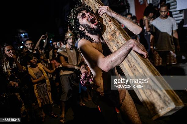 Catholic devotees reenact the sufferings of Jesus Christ during a Good Friday procession on a street in the Rocinha community of Rio de Janeiro,...