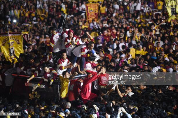 Catholic devotees suround the statue of the Black Nazarene on a carriage during the annual religious procession in honour of the Black Nazarene in...