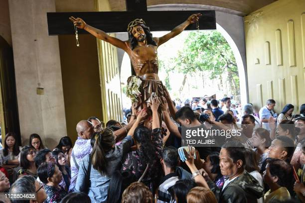 Catholic devotees touch a crucifix as they pray on 'Ash Wednesday' at a church in Manila on March 6 2019 The 40day period of Lent begins on Ash...