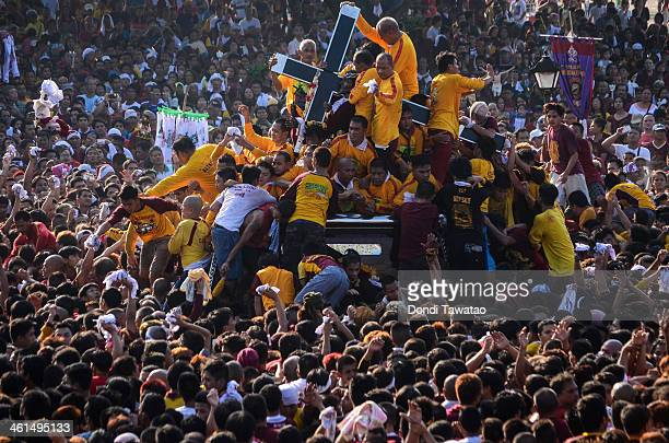 Catholic devotees try to get near the Black Nazarene on January 9 2014 in Manila Philippines Devotees march barefoot as a sign of sacrifice during...