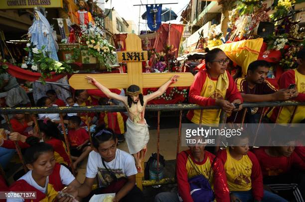 Catholic devotees wait for the start of the blessing of the replicas of the Black Nazarene near Quiapo church in Manila on January 7 ahead of the...