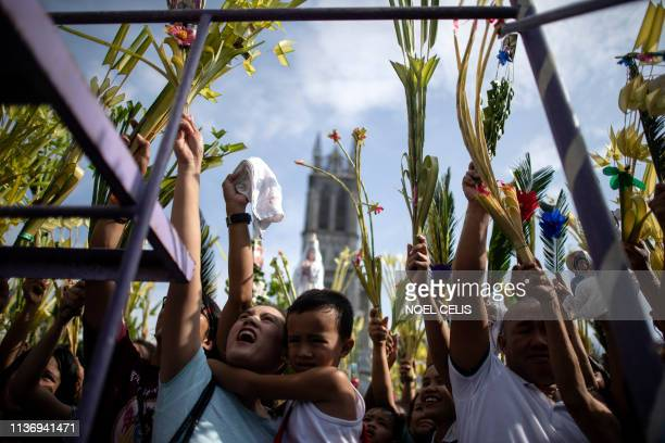 Catholic devotees wave their palm fronds as a church layman blesses palms during Palm Sunday celebrations at the Our Lady of Lourdes Grotto church in...