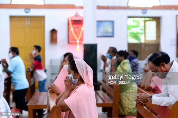 Catholic devotees wear face mask attend the Holy Mass at the Saint Joseph's Church on the first day after the reopening of religious services after...