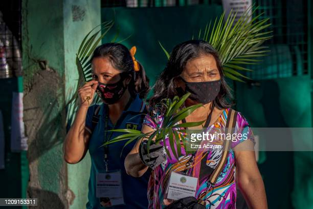 Catholic devotees wearing facemasks hold palm fronds outside their homes as they wait for a priest to bless them with holy water as they celebrate...