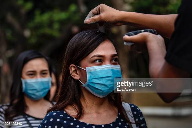 Catholic devotees wearing protective masks fall in line to have their head sprinkled with ash during Ash Wednesday services at a church on February...