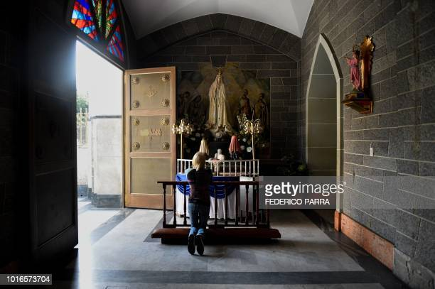 A catholic faithful attends mass at La Coromoto Church in Caracas on August 12 2018 The shortage of cash in the country has forced churches to accept...