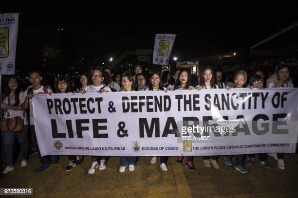 Catholic faithful carry a banner as they join a 'march for life' at a park in Manila early on February 24 2018 Thousands of Roman Catholic faithful...