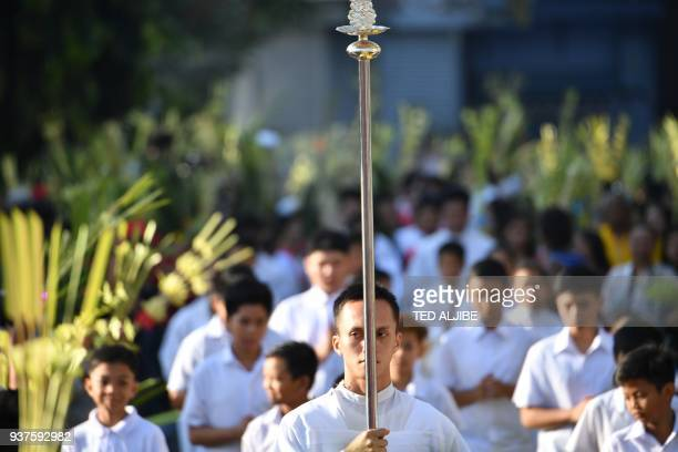 TOPSHOT Catholic faithful holding palm leaves walk to the church as part of the traditional lenten devotion in Manila on March 25 2018 Palm Sunday...