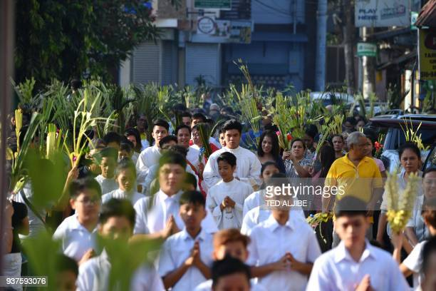 Catholic faithful holding palm leaves walk to the church as part of the traditional lenten devotion in Manila on March 25 2018 Palm Sunday marks the...