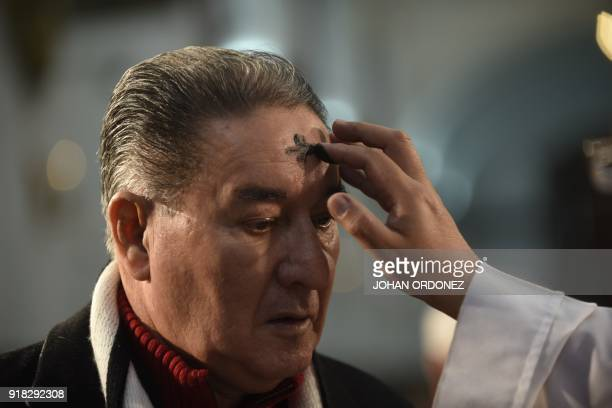 A Catholic faithful participates in the traditional Ash Wednesday ceremony at the Metropolitan Cathedral in downtown Guatemala City on February 14...