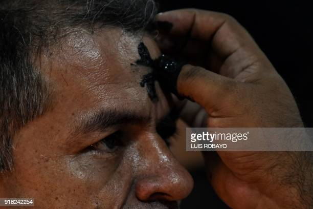 A Catholic faithful participes in the celebration of Ash Wednesday in Cali Colombia on February 14 2018 Ash Wednesday marks the Christian period of...