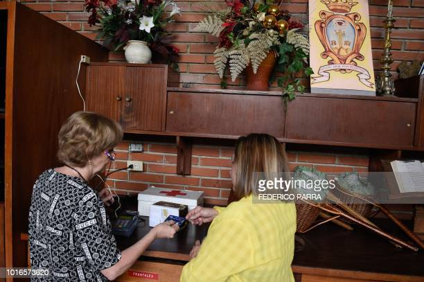 A catholic faithful pays the tithe with a debit card at La Coromoto Church in Caracas on August 12 2018 The shortage of cash in the country has...