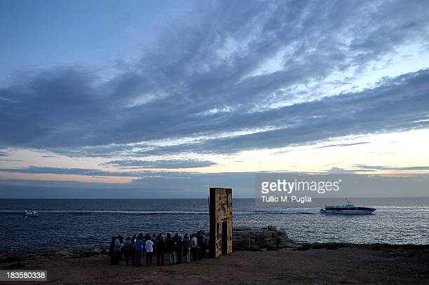Catholic faithful pray in front of the Porta d'Europa Monument on October 7 2013 in Lampedusa Italy The search for bodies continues off the coast of...