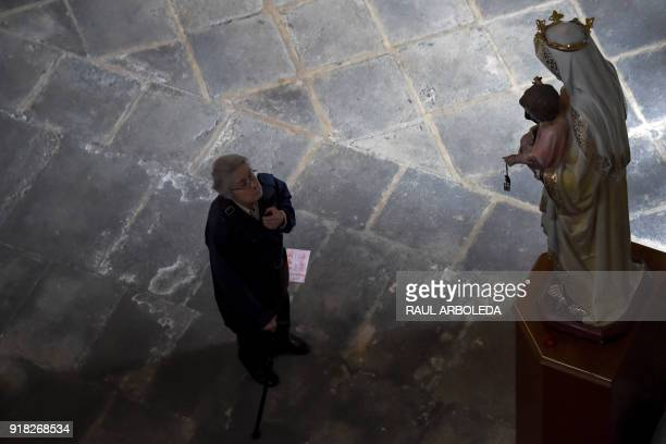 A Catholic faithful stands in front of a Virgin and Child sculpture during the celebration of Ash Wednesday at Our Lady of Lourdes Sanctuary in...