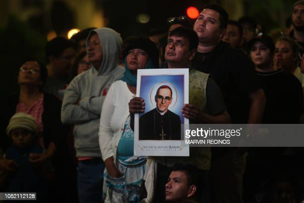 Catholic faithful watch a televised screening of the ceremony of the canonization of blessed Monsenor Oscar Romero at the Square Gerardo Barrios in...