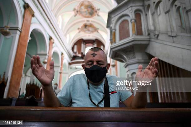 Catholic faithful wears a face mask during the celebration of Ash Wednesday in Cali, Colombia, on February 17, 2021. - Ash Wednesday marks the...